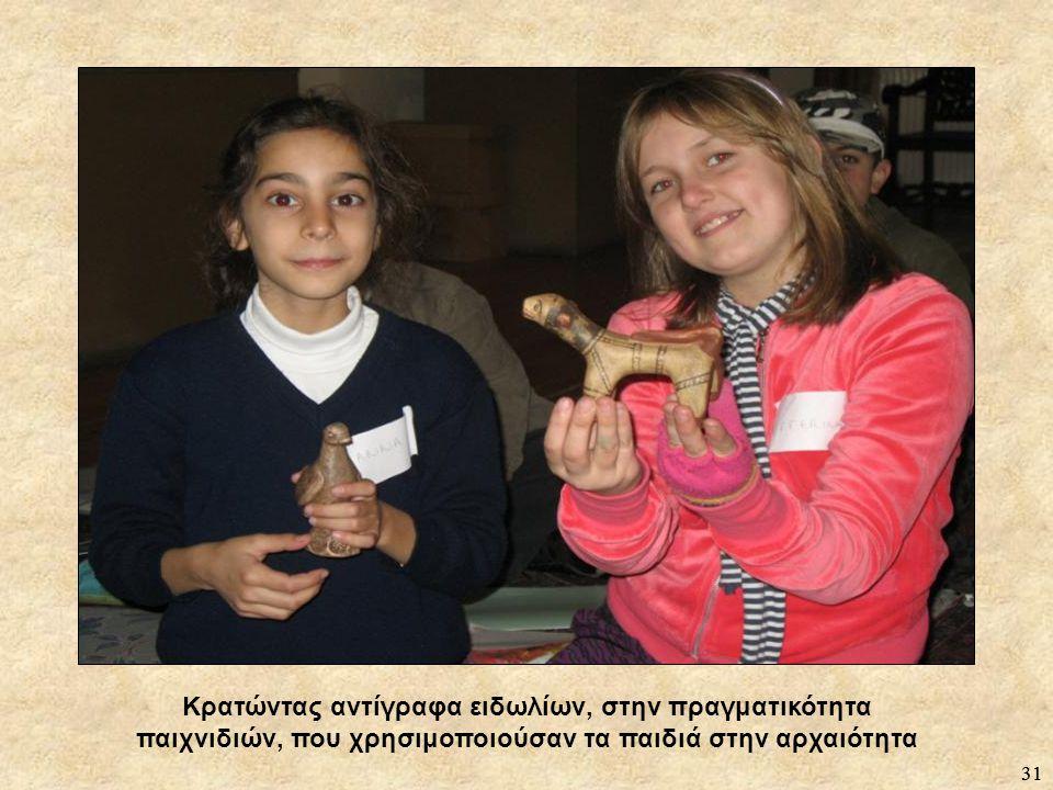 Κρατώντας αντίγραφα ειδωλίων, στην πραγματικότητα παιχνιδιών, που χρησιμοποιούσαν τα παιδιά στην αρχαιότητα